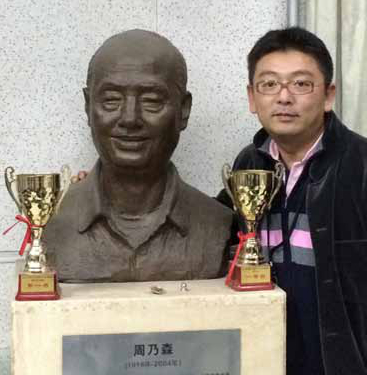 Cellist Yao Zhao poses with a statue of his grandfather before a San Diego Symphony concert at Tsinghua University in Beijing, China. The statue was erected upon the grandfather's death to honor his long years service as the university's band director. The grandfather is the one with the bigger smile.